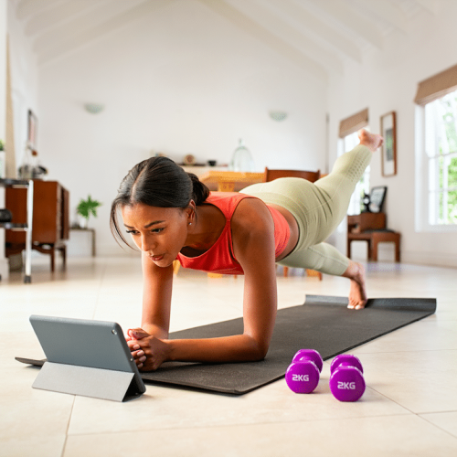 mixed-race-woman-doing-plank-and-watching-online